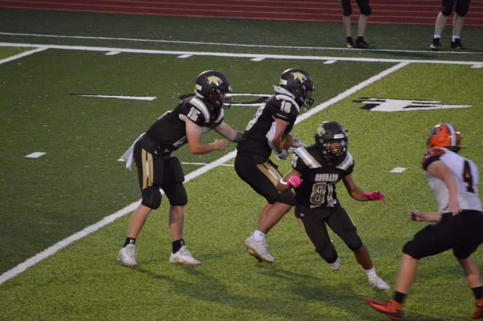 MACON TAKES COMEBACK WIN-Drew Mallett (#15 in Brown) hands off to Robert Goehl (#18) during Clarence Cannon Conference football play at Highland. Brandon Holder (#81) blocks on the play. The Tigers scored in the final two minutes, completing a 32-20 come from behind victory. Highland rushed for 281 yards. Drew Mallett rushed 7 times for 164 yards and a touchdown and passed for 58 yards and two scores. Robert Goehl rushed 24 times for 131 yards and a touchdown on the 2021 Highland football Senior Night. Photo by Brenda Mallett.
