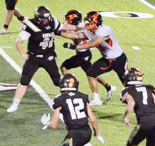 LOOK MA! ONE HAND!: sophomore Linebacker Zander Johnson, #40, single-handedly holds off two Palmyra Panthers. The Highland Cougars brought down the Palmyra Panthers in a 24-20 victory Friday night, launching them to second place in their district, just behind Marceline.